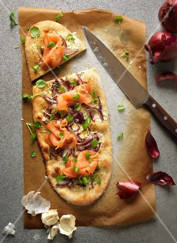 Sour cream pizza with smoked salmon, onions and cress