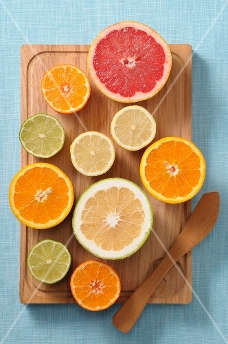 Halved citrus fruits on a wooden board