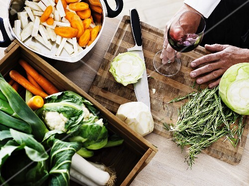 A man with a glass of red wine preparing vegetables and herbs
