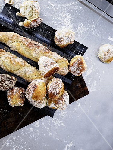 Freshly baked rolls and baguettes on a baguette baking tray