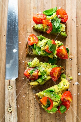 Bread corners topped with guacamole and tomatoes
