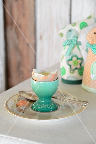 Boiled egg with top removed in turquoise eggcup in front of textile rabbit-shaped egg warmers