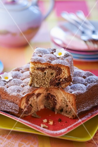Marble cake with icing sugar, partly sliced
