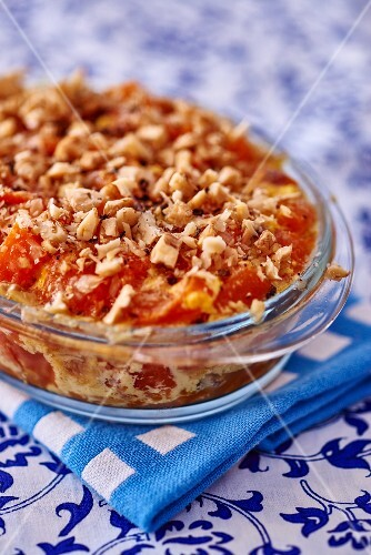 Tomato gratin with chopped nuts in a glass baking dish
