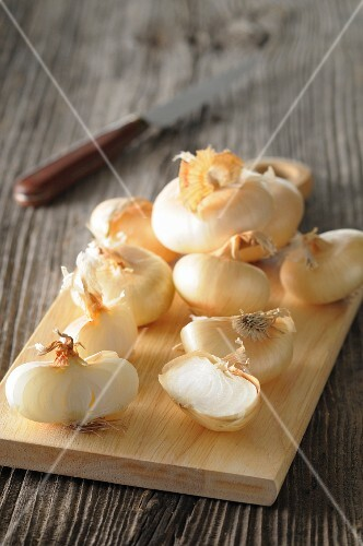 White onions, partially sliced, on a chopping board