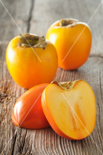 Persimmons, whole and halved, on a wooden surface