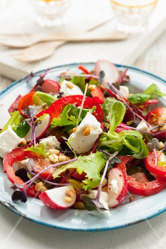 Greek salad with peppers, radishes and pine nuts
