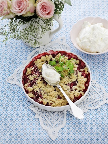 Raspberry and rhubarb crumble with whipped cream