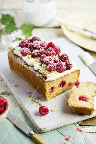 Raspberry cake with icing sugar and pistachios, sliced