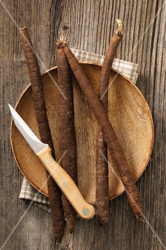 Fresh black salsify on a wooden plate with a knife