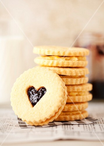A stack of jam and cream sandwich biscuits with heart-shaped windows