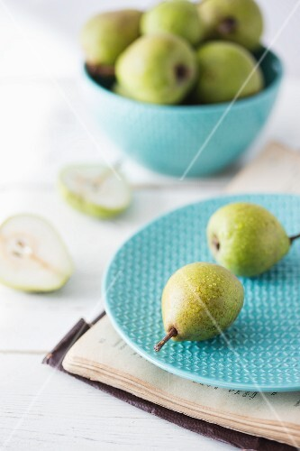 Fresh ripe pears on a plate and in a bowl