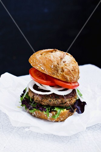 A burger with beef, onions and tomatoes