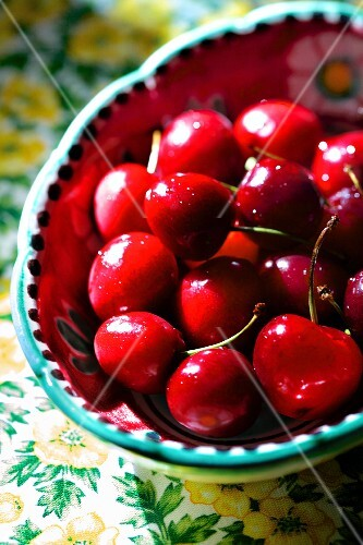 Bright red cherries in a colourful ceramic bowl
