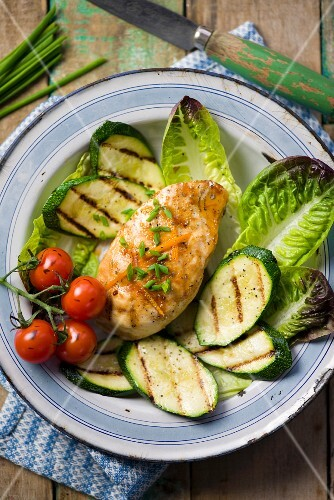 Chicken breast with an orange and honey glaze on a bed of grilled vegetables and lettuce leaves