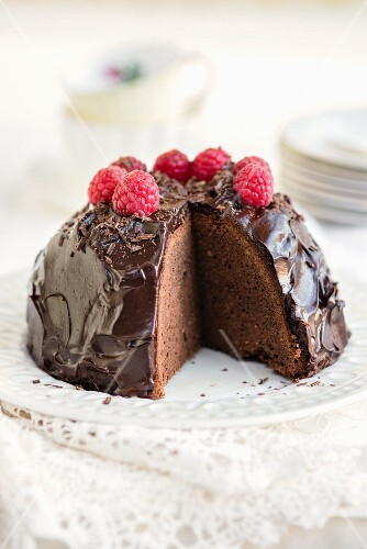 Gluten-free cake with avocado, cocoa and honey glaze and fresh raspberries, sliced