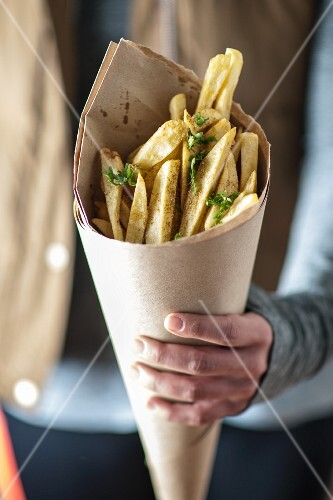 A person holding a cone of herb chips