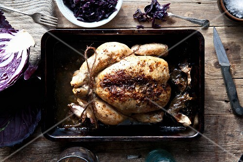 Oven-roasted chicken in a baking tin with a red cabbage medley (seen from above)