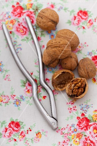 Walnuts with a nutcracker on a floral cloth