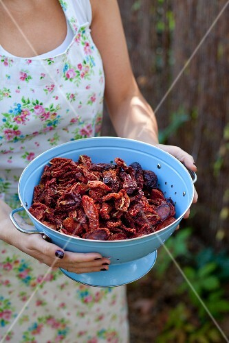 A woman holding dried tomatoes in a colander