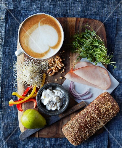 Ingredients for a turkey sandwich (turkey ham, pears, cottage cheese, pepper, walnuts, alfalfa sprouts and red onions) with a cafe latte