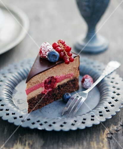 A slice of chocolate mousse cake with rum, raspberries, blueberries and redcurrants