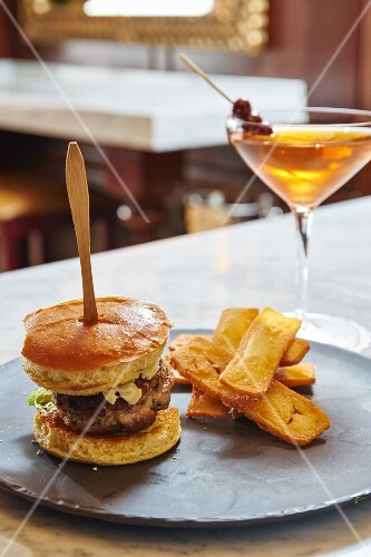 A cheeseburger and potato wedges with a Martini in a restaurant