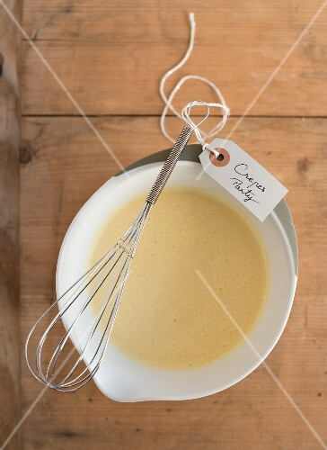 Crêpe batter in a bowl with a whisk and a label for a party
