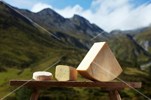 Alpine cheese against a mountain backdrop