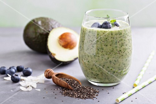 Green avocado and spinach smoothie with blueberries and chia seeds