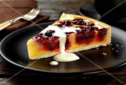 A slice of cherry and vanilla pudding tart with cream