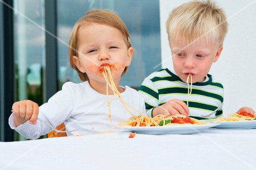 Two small children eating spaghetti with tomato sauce