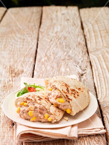 Pita bread filled with tuna and sweetcorn salad on a plate