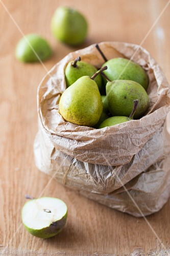 Fresh ripe pears in a paper bag on a wooden surface