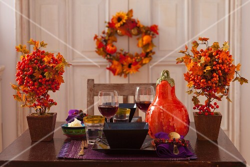 Table set for two autumnally decorated with pumpkin and berries