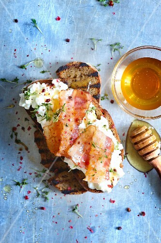 Grilled bread topped with cottage cheese, bacon and honey
