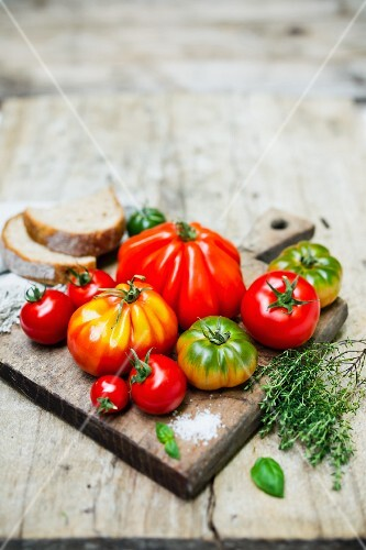Various tomatoes on a chopping board with salt, thyme and bread