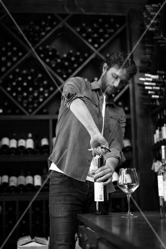 A sommelier opening a bottle of wine (black and white shot)