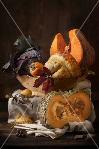 An autumnal arrangement featuring pumpkins, cabbage, persimmons and pears