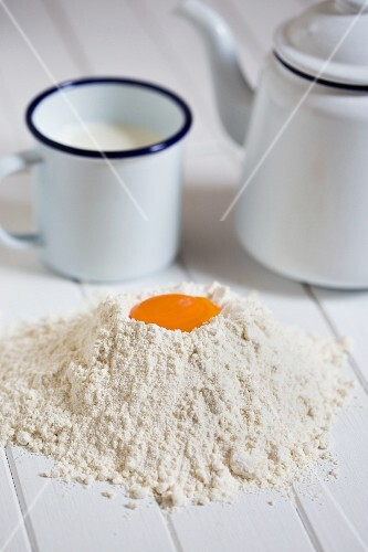 Egg yolks in heap of flour