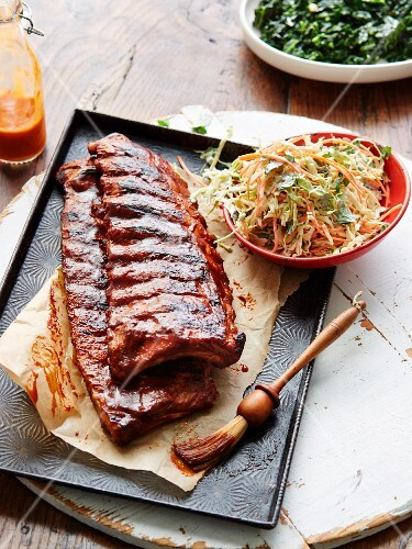 Marinated spare ribs on a baking tray with a bowl of coleslaw