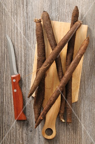 Black salsify on a chopping board next to a knife