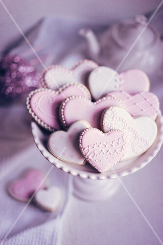 Pastel coloured heart-shaped biscuits on a biscuit stand