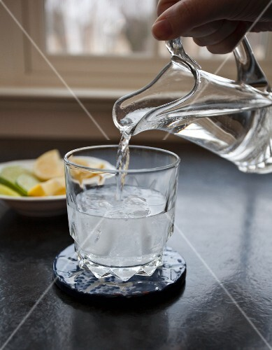 Soda water being poured into a cocktail glass with vodka and ice cubes