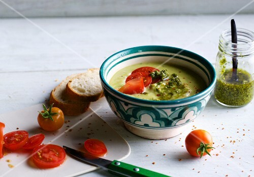 Cold avocado and cucumber soup with pesto and tomatoes