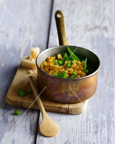 A copper saucepan with wheat risotto and peas
