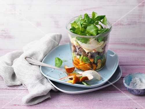 A layered chanterelle mushroom salad with chestnuts in a glass