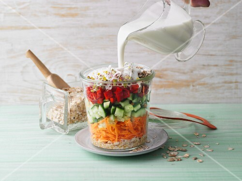 Yoghurt sauce being poured over multigrain vegetable muesli in a jar