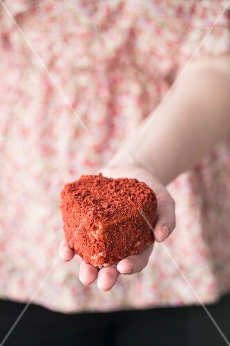 A woman holding a heart-shaped Red Velvet cake