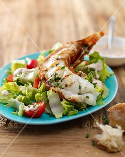 A langoustine tail on a bed of salad